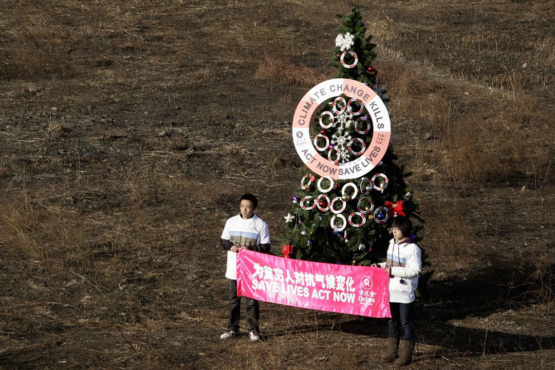 Volunteers hold a banner in front of a Christmas tree on a dried-up riverbed on the outskirts of Beijing