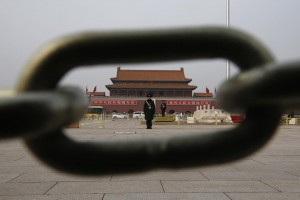 A paramilitary solder standing guard is seen through a chain surrounding a flagpole of China's national flag on Tiananmen Square in Beijing